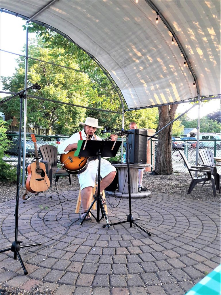 "Al Ynigues sings with guitar at a ""Free Open Mic"" at Local Roots Cafe in Richfield, MN. This is a social distancing outdoor venue held on Wednesday evenings."